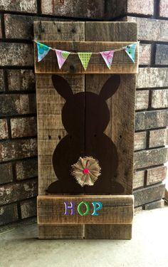 Hop! Hop! Hop! This item is handmade from reclaimed pallet wood. Hand painted bunny with a cute burlap button tail and Spring bunting added for some extra charm. Measures approximately 24 tall x 11 wide. Has wire on back for hanging or can simply lean on shelf / mantle. No two signs alike due to being handmade from reclaimed wood. I make no attempts to hide imperfections of the reclaimed wood. Each one will be one of a kind.