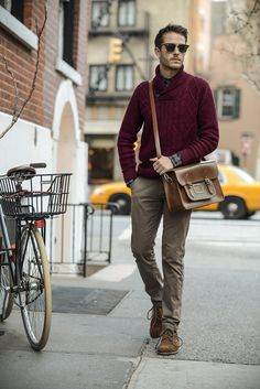 Opt for a dark red shawl neck sweater and brown chino pants for your nine-to-five. Rock a pair of brown suede derby shoes for a masculine aesthetic.   Shop this look on Lookastic: https://lookastic.com/men/looks/shawl-neck-sweater-long-sleeve-shirt-chinos/14548   — Black Sunglasses  — Red and Navy Plaid Long Sleeve Shirt  — Burgundy Shawl Neck Sweater  — Brown Leather Messenger Bag  — Brown Chinos  — Brown Suede Derby Shoes