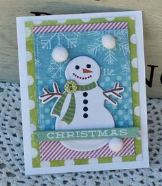 """Another way to add the extra special touches to hand-deliverable cards is to layer your chipboard embellishments and to add a pom pom or two to the snowflakes on the patterned paper. It now """"feels"""" like snow!"""