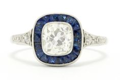 The Oakland antique 1 carat cushion diamond Art Deco engagement ring is a breathtaking and captivating example of Jazz Age style at it's best. The sizzling center boasts a sparkling old mine cut diamond with amazing clarity and a delightful warmish color, securely set in a platinum target surrounded by velvety blue French cut sapphires kissed with dainty milgrain. #artdeco #engagementring #bellarosagalleries #diamond #sapphire #haloring #targetring #engagementrings #1carat #love #ido #engaged Estate Engagement Ring, Antique Engagement Rings, Diamond Engagement Rings, Cushion Diamond, Diamond Art, 1 Carat, Natural Sapphire Rings, Jazz Age, Hand Jewelry