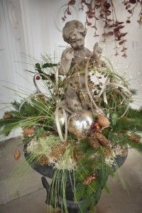 Cherub surrounded by Christmas greenery, pine cones, and mercury balls