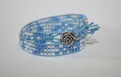 Doppio giro di perline 11/0 azzurre bianche e argento, cotone cerato azzurro e bottone rosetta color argento.