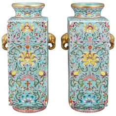 Pair of Chinese Famille Rose Glazed Porcelain Vases 19th Century. Each of squared section rising to a round neck and set on a round foot rim, the sides with gilt elephant head handles, enameled with scrolling lotus on leafy stems all on a turquoise field, base with a Jiaqing seal mark. Height 8 7/8 inches.
