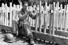 Private Alfonton Ortega, from Los Angeles, sets up wooden crosses which will be used as grave markers.  Normandie.  1944