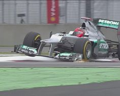 Sparks fly as Michael Schumacher bounces over the kerbs