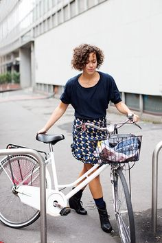 The sartorialist, 25 September 2012 at Marni, Milan. Woman in a patterned skirt with her bike.