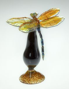 """Gold Dragonfly Bottle"" Art Glass Perfume Bottle Created by Loy Allen A dragonfly spreads its golden wings in lifelike lampworked detail, perched atop the stopper of a footed blown glass bottle in black and gold."