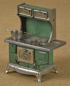 Kenton cast iron and nickel Favorite toy stove, 9 1/2'' h., 7 1/2'' w., together with miniature cookware.