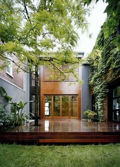 Beautiful home exterior shaded by trees and featuring a mixture of wood, concrete and brick | Natalie Dionne