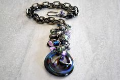 Amethyst beads and glass teardrops dangle below a glossy gunmetal chain, clustered above a striking art glass disc in swirling shades of purple and blue with hints of green. The disc is recycled art glass that has been flame-worked and hand sculpted. Gunmetal hook and eye clasp.