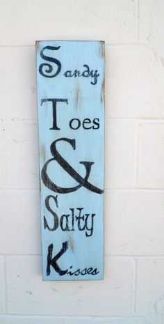 "This is an approximate 7.5"" wide x 27"" tall rustic, distressed beach-y decor sign. It is made out of reclaimed wood, painted light blue, distressed, hand-painted ""Sandy Toes  Salty Kisses"", and then protected with a clear coat varnish for easy cleaning and durability.  $32.00"