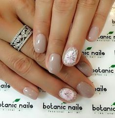 Nude nail art with flower details on top. Let your nails stand out by painting flowers and adding embellishments above the nude polish.