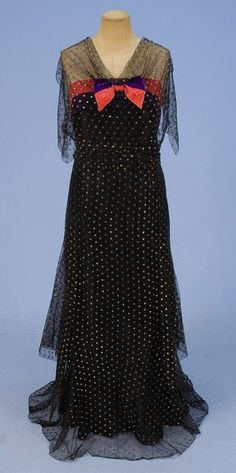METALLIC DOTTED EVENING DRESS, 1930's. Black tulle with all over gold embroidered dots having sheer bodice with shoulder and side flounce over pink and purple velvet bands with central bow with flared skirt, side closure and silk under-skirt. Front