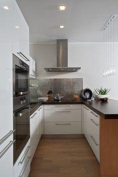 Kuchyňská linka disponuje širokým jídelním pultem, který dobře poslouží i k přípravě jídel. Opět zde hrají svou roli neutrální barvy. Pro zvýraznění zde byla použita zrcadlová mozaika.