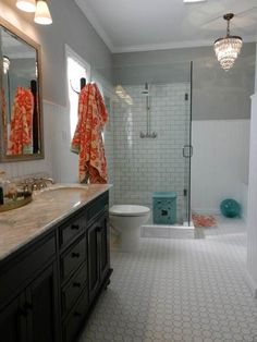 master bathroom remodel - white subway tile w/ colored grout, glass shower enclosure, vintage sideboard vanity, marble counter & under-mount sinks, opal glass vanity lights, crystal chandelier, pine beadboard wall & whirlpool tub enclosure, tub bookcase, ceramic garden stool in shower, coat rack for towels. good source list