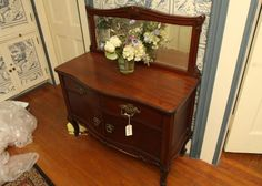 """Two drawer two door mirrored back server with beveled glass, dovetail construction, and ornate metal pulls, on casters 44""""x18""""x46"""" tall."""