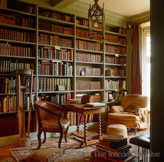 The shelves of this library are filled with old leatherbound books and a shabby armchair in the corner by the window provides a perfect spot for reading