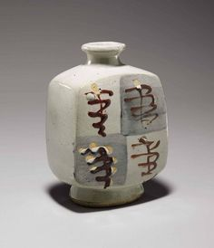 Bernard Leach (1887-1979) <br />A stoneware molded bottle-vase <br />(Mid-20th century), impressed monogram <i>BL</i> on the foot ring and with another impressed seal<br />The flattened rectangular bottle-vase with narrow waisted neck and oval foot, decorated with a salt glaze and underglaze-blue quadrants decorated with raised red-enamel motifs; sealed on inside edge of the foot ring<br />7 3/8in. (18.8cm.) high <br />
