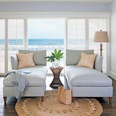 Duel Chaise In Soft Blue Accented With Natural Toned Pillows Rug And Lamp Shade