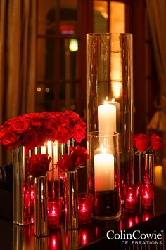 Metallic floral vessels filled with red roses look elegant in soft candlelight.