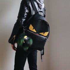 Fendi black monster eyes backpack with Funich bag bug fur charm.