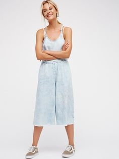 Skatergirl Jumper | Cool girl racerback denim jumper featuring a dramatic wide leg and frayed edges for a lived-in look. Adjustable straps with simple button closures. Side pockets.