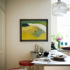 Kitchens: White Kitchen with Gray Worktop also Glass Pendant Light plus Beach Painting and Red Stools