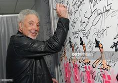 Singer Tom Jones signs the wall at AOL Studios when he visits for AOL Build Presents Tom Jones 'Long Lost Suitcase' at AOL Studios In New York on...