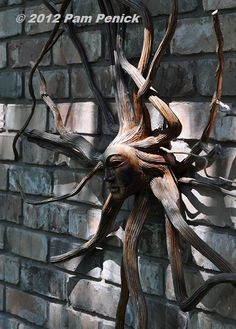 Sculpture made from tree roots hangs on a brick wall