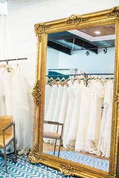 Bridal boutique with brick walls, and a large vintage gold mirror