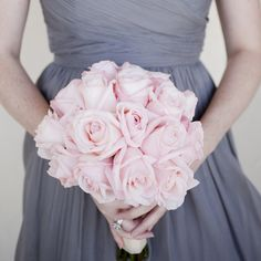 The bridesmaids' pale pink rose bouquets complemented their gray dresses.