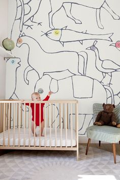 This nursery has a simple square crib, circular geometric rug, midcentury upholstered chair and a bold black and white animal mural with subtle splashes of color.