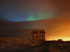 Luzes do Norte na Islândia, na península de Reykjanes. As nuvens, as manchas azuis no céu, as luzes verdes do norte e o reflexo alaranjado das luzes da cidade de Reykjavik, todos misturados em um show de luz multicolor.  Fotografia: Fred Schalk.