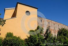 Photo made in Padua in Veneto (Italy). In the image you see, in the foreground, the trees beyond which a yellow building with a circular window in the center of the facade leans a high and ancient walls to his right. Both buildings, the oldest and the most recent stand out in the intense blue of the sky.