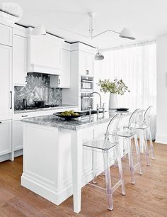 White kitchen with bold marble countertops and backsplash {PHOTO: Stacey Brandford}