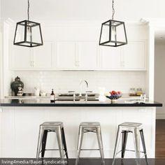 Durch die Elemente aus Metall bekommt die weiße Einbauküche eine coole Lässigkeit Die Laternenleuchten wirken rustikal und passen gut zu der schwarzen…