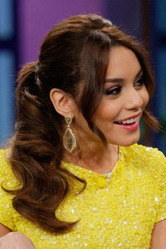 Backcomb your hair and sweep it into a low ponytail, then curl sections of it with a wide curling iron. Shake out the curls for loose waves, and accessorize with statement earrings for all-out glamour. TeenVogue.com