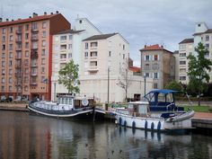 Roanne: Marina with its moored boats, quay, trees and buildings of the city - France-Voyage.com