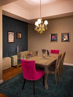 Bright fuchsia dining chairs add glam to this contemporary dining room. Each upholstered chair is accented with nail-head trim, while a navy blue accent wall and area rug ground the space.