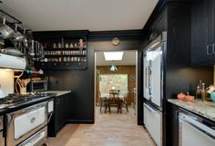 Black also makes for a beautiful, artistic backdrop for appliances to stand out, like this black stained ash kitchen with contrasting white Heartland appliances.