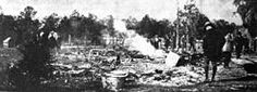 =A black and white photograph of ashes from a burned building with several people standing nearby; trees in the distance--> Rosewood Massacre