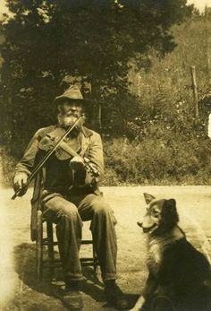 Vintage photo, old-time fiddler with his dog.