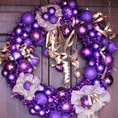 This beautiful purple garland wreath is themed for Christmas and has White lights weaved into the framework. The balls on the wreathe are in purple and are considered shatterproof. Gold ribbon runs throughout the wreath and hangs from the center. By SummerWilson8