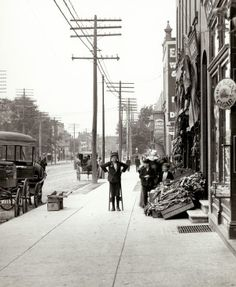 Boy with stilts standing in front of the F.J. Voepel Market at 4874 Easton (M.L. King) Avenue east of Euclid. Southeast corner. (1906)
