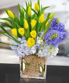 Like the early morning sun majestically rising above a misty spring dawn, these vivid yellow tulips and vibrant daffodils shine bright above gentle clouds of hydrangeas and purple hyacinth in this fantastic springtime bouquet!