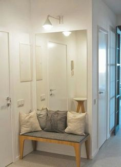 a small entryway needs only a comfy bench and a large mirror to make it look bigger