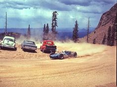"""1968 Pikes Peak Hill Climb - Mario Andretti driving his Brawner-Ford """"Hawk"""" Special past parked cars at a switchback above George's Corner on Pikes Peak.  Andretti took fourth place overall in the legendary race. #PPIHC #PikesPeak"""
