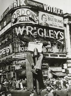 An American soldiers sits on top of a traffic light in London to celebrate the news of the end of the war.