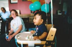 toddler smiling on high chair photo