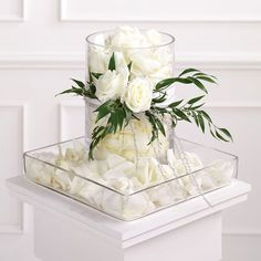 This could be a simple yet interesting centerpiece.  White rose petals in a cylinder vase and square container, with roses and italian ruscus attachment.